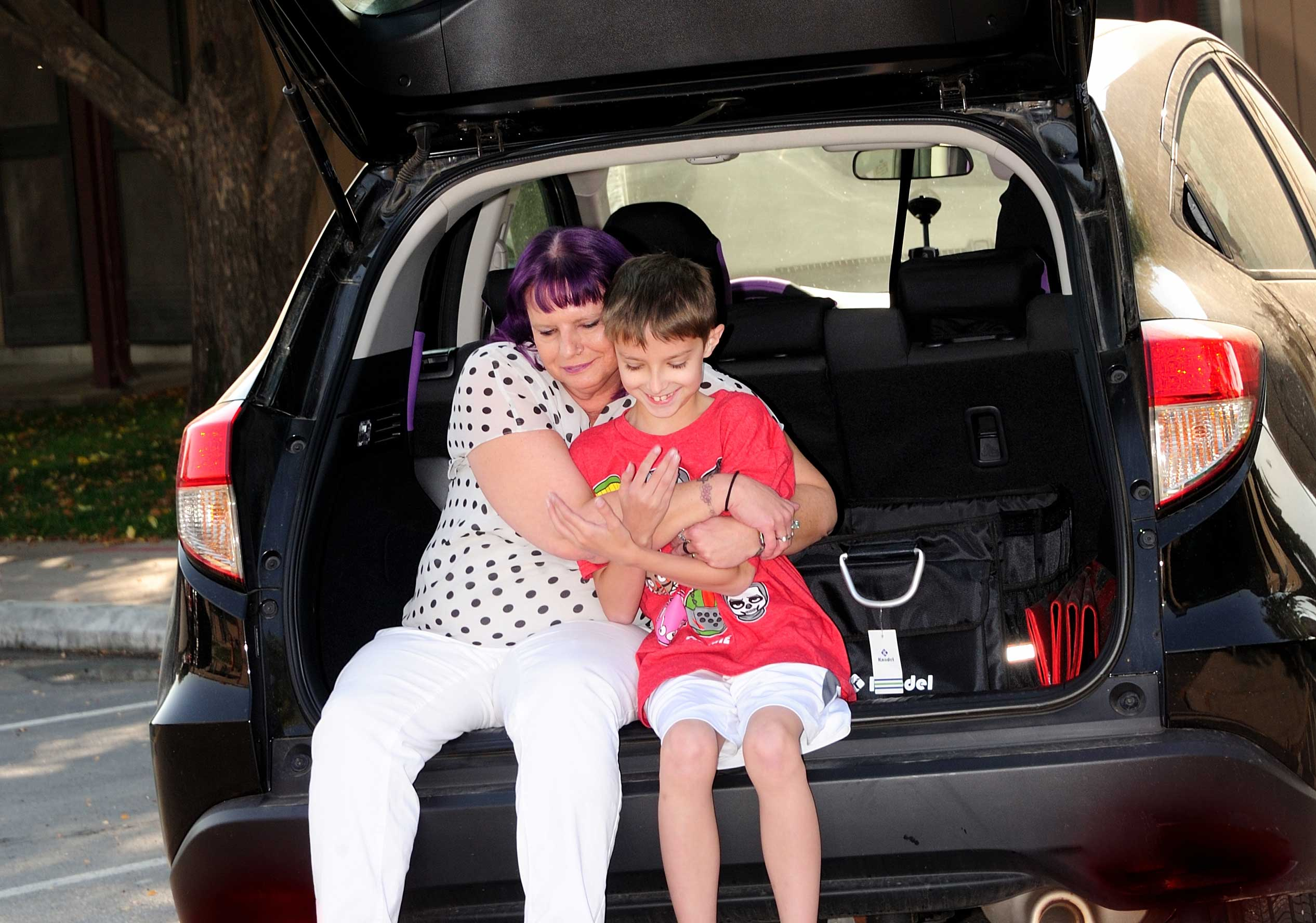 Amber Person hugging child in back of a vehicle