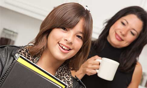 Young person holding book with person standing behind her smiling holding a coffee mug