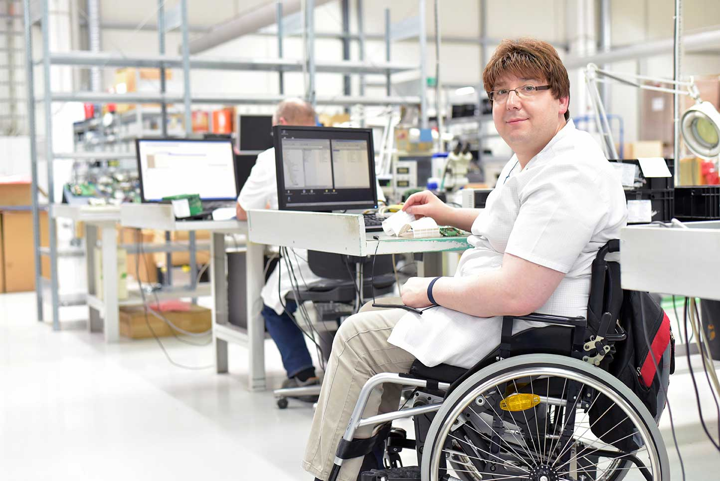 person in wheelchair at work station